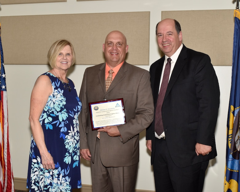 Jeff Blackstock (center) receives the 2019 Michael G. Simodejka Outstanding Sustainment/Logistics Manager of the Year award from Thomas Rudowsky (right), NAVAIR Sustainment director, and Pat Simodejka (left), widow of the late Michael Simodejka, during a ceremony at Joint Base McGuire-Dix-Lakehurst, New Jersey July 31. (U.S. Navy photo by Sherry Jacob)