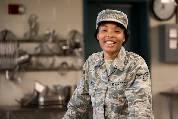 Airman posing for a photo in with kitchen equipment in the background