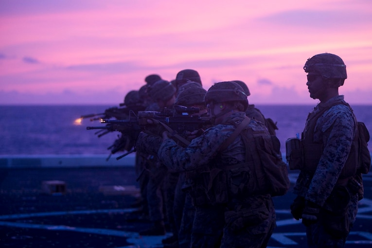 Marines stand in a line shooting from rifles.