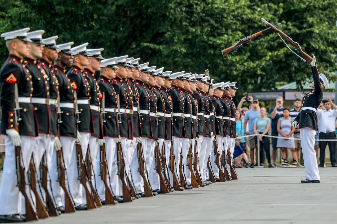 Marines stand in a line as one Marine facing them catches a rifle mid-air.