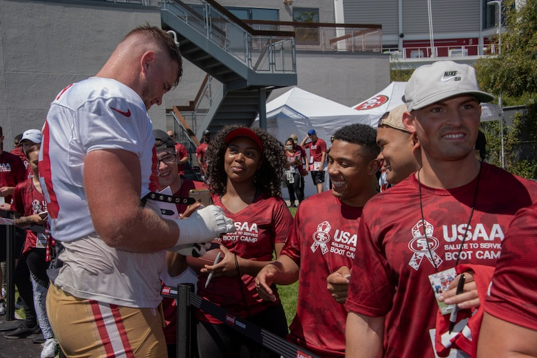 San Francisco 49ers offensive lineman Mike McGlinchey signs autographs for Airmen from Travis Air Force Base, California, Aug. 13, 2019, during the Salute to Service Boot Camp event in Santa Clara, California. The event provided Airmen with an opportunity to interact with NFL players and compete against one another in a variety of athletic drills. (U.S. Air Force photo by Tech. Sgt. James Hodgman)