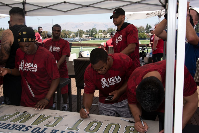 U.S. Air Force Airmen from Travis Air Force Base, California, sign a 'Salute to Service' banner Aug. 13, 2019, during the Salute to Service Boot Camp in Santa Clara, California. The event provided Airmen with an opportunity to interact with NFL players and compete against one another in a variety of athletic drills. (U.S. Air Force photo by Tech. Sgt. James Hodgman)