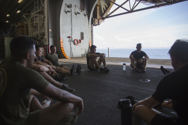 """PACIFIC OCEAN (Aug. 8, 2019) Marines and Sailors with the 31st Marine Expeditionary Unit have a guided discussion with Lt. Cmdr Jason Weatherwax, Chaplain with the 31st Marine Expeditionary Unit, after """"Chap's Fit"""", a daily workout and discussion group focusing on spiritual toughness, aboard the amphibious assault ship USS Wasp (LHD 1). Wasp, flagship of the Wasp Amphibious Ready Group, with embarked 31st MEU, is operating in the Indo-Pacific region to enhance interoperability with partners and serve as ready-response force for any type of contingency, while simultaneously providing a flexible and lethal crisis response force ready to perform a wide range of military operations. (Official U.S Navy photo by RP3 Anthony Wood-Casella)"""