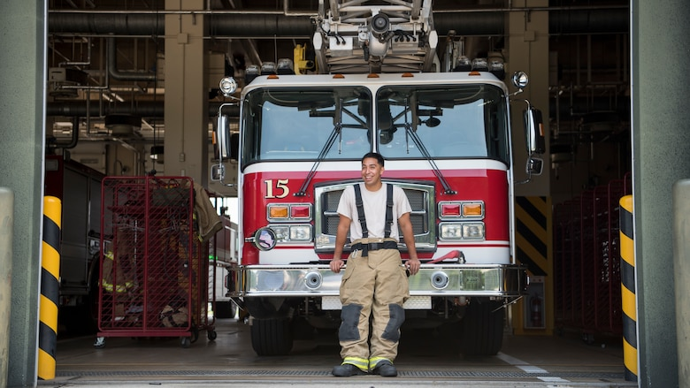 U.S. Air Force Airman 1st Class Adam Cardona, a 35th Civil Engineer fire protection journeyman, pauses for a photo in front of a fire truck at Misawa Air Base, Japan, Aug. 7, 2019. Cardona's leadership makes training exercises a top priority due to the base's location, enhancing his professional growth. (U.S. Air Force photo by Senior Airman Collette Brooks)