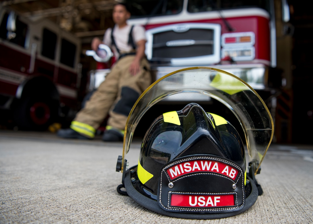 USAF Cardona's fire protection helmet sits on the ground in front of a fire truck at Misawa Air Base, Japan, Aug. 7, 2019. Cardona expressed Misawa City residents made him instantly feel like a part of the community due to their generosity, kindness and easy going personalities. The demeanor of local Japanese members inspired Cardona to be more humble, understanding and thoughtful when interacting with others. (U.S. Air Force photo by Senior Airman Collette Brooks)