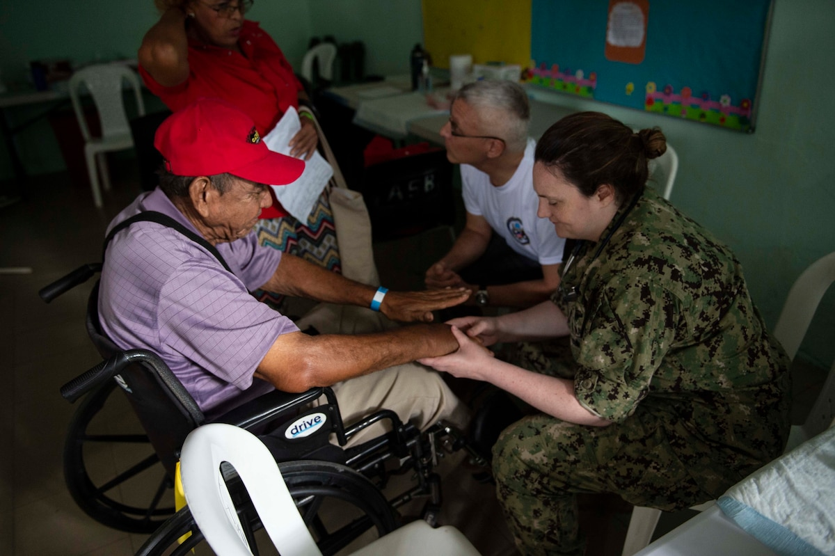 A military doctor examines a patient.