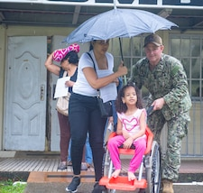 A military member pushes a child in a wheelchair.