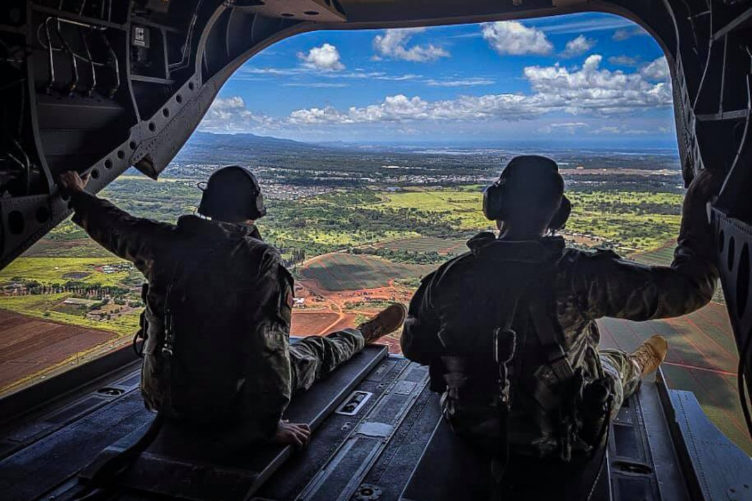 Two soldiers sit in a helicopter as it flies over land.