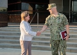 Navy Admiral greets Defense Logistics Agency Chief of Staff  in front of Land and Maritime Headquarters building.