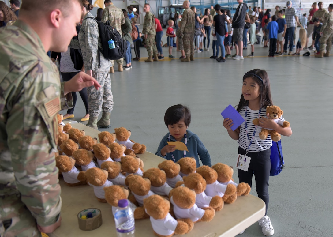 A child receives a teddy bear and a stamp for her paper while in-processing during the 'kids deployment line' at RAF Mildenhall, England, Aug. 9, 2019. The third annual Operation Together and Ready, helped the families of Team Mildenhall  learn what Airman go through to prepare for a deployment. (U.S. Air Force photo by Senior Airman Benjamin Cooper)