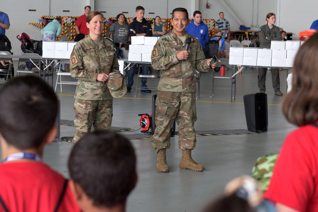 Chief Master Sgt. Kathi Glascock, 100th Air Refueling Wing command chief, and Col. Troy Pananon, 100th ARW commander, speak to children at the 'kids deployment line' at RAF Mildenhall, England, Aug. 9, 2019. Pananon and Glascock took turns speaking to the children and getting them ready to begin their day of deployment activities. (U.S. Air Force photo by Senior Airman Benjamin Cooper)