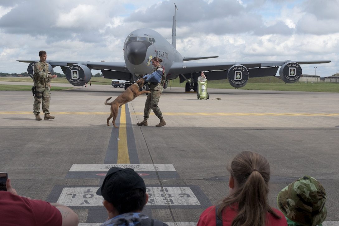 From the left: Staff Sgt. Camron Quaranto, 100th Security Forces Squadron military working dog handler, and his partner Karo perform a bite demonstration with Tech. Sgt. Melissa Burns, 100th SFS MWD kennel master, during the 'kids deployment line' at RAF Mildenhall, England, Aug. 9, 2019. After the demonstration the children toured a KC-135 Stratanker, a CV-22 Osprey and an MC-130J Commando II. (U.S. Air Force photo by Senior Airman Benjamin Cooper)