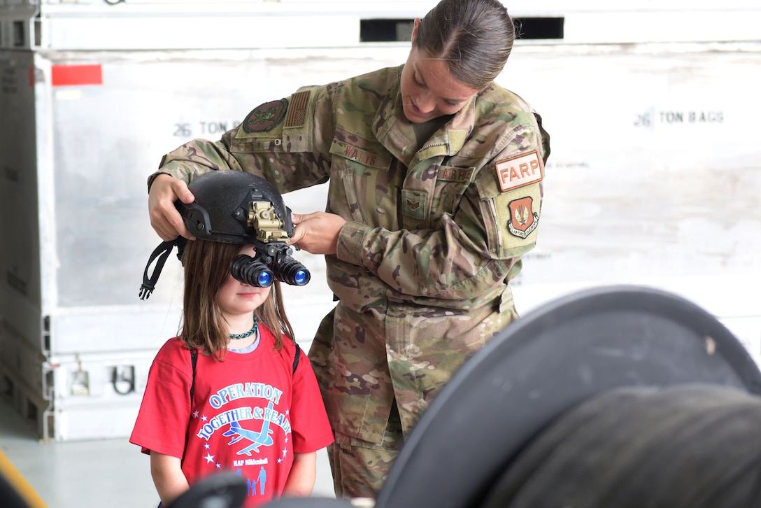 Senior Airman Tori Watts, 100th Logistics Readiness Squadron fuels distribution operator, helps a child try on night-vision goggles during the 'kids deployment line' at RAF Mildenhall, England, Aug. 9, 2019. The children were able to understand how Forward Arming and Refuling Point Airmen perform their job at night. (U.S. Air Force photo by Senior Airman Benjamin Cooper)