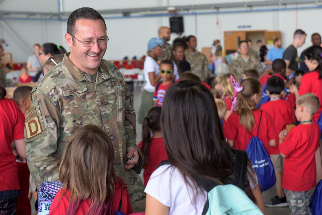 Master Sgt. Jeremiah Bybee, 100th Comptroller Squadron first sergeant, presents a coin to a child during the 'kids deployment line' at RAF Mildenhall, England, Aug. 9, 2019. All of the children present received a coin from one of the wing's first sergeants. (U.S. Air Force photo by Senior Airman Benjamin Cooper)