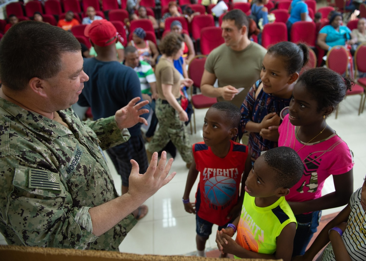 A U.S. military person speaks to children.