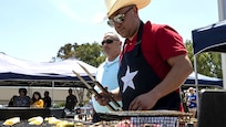 Marine Gunnery Sgt. Mario Cardenas, with Provost Marshal's Office, Headquarters and Headquarters Squadron, prepares lunch for the H&HS Barbecue Cook-off at Marine Corps Air Station Miramar, California.