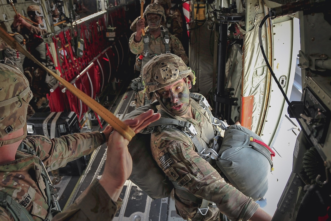 A soldier prepares to jump out of a plane.