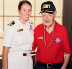 Navy Lt. j.g. Kathleen Spyrnal, an officer programs operations officer assigned to Navy Recruiting District San Antonio, poses with WWII Merchant Marine Ray Denison during an Alamo Honor Flight Breakfast at a local restaurant Aug. 14. Attended by other WWII veterans, the breakfast also served as a venue to celebrate Denison's 100th birthday. Denison, a long-time city resident and native of Eagle Pass, Texas, joined the U.S. Merchant Marines on Memorial Day 1942 and served till November 1945.  While serving, he held a reserve commission as a lieutenant junior grade in the U.S. Navy.
