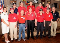 Navy Lt. j.g. Kathleen Spyrnal, an officer programs operations officer assigned to Navy Recruiting District San Antonio, poses with members of Alamo Honor Flight during their monthly breakfast Aug. 14. The breakfast also served as a venue to celebrate WWII Merchant Marine Ray Denison's 100th birthday (first row, third from right).