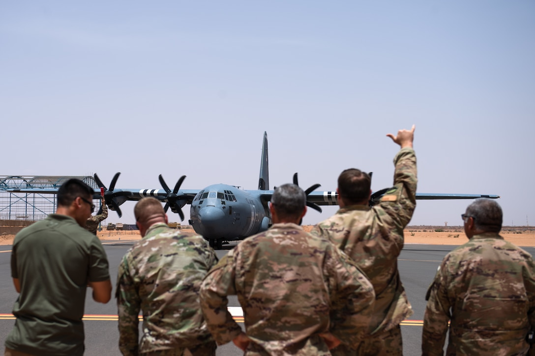 U.S. Air Force Airmen assigned to the 409th Air Expeditionary Group watch as a C-130J Super Hercules taxis in at Nigerien Air Base 201, Agadez, Niger, Aug. 3, 2019. The C-130 landing marked the next step in airfield evaluations by starting Visual Flight Rules operations at the base. (U.S. Air Force photo by Staff Sgt. Devin Boyer)