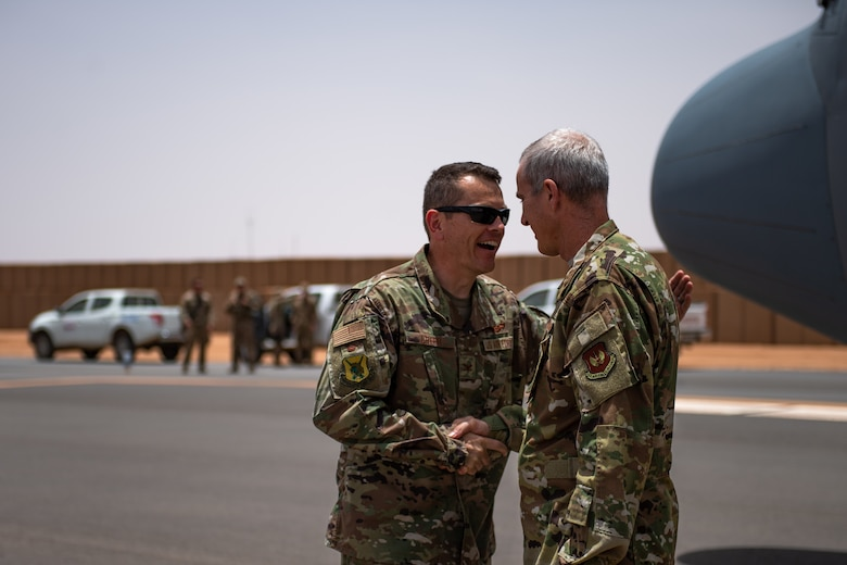 U.S. Air Force Col. Jonathan Creer, 409th Air Expeditionary Group commander, welcomes Col. Steven J. Jantz, 435th Air Ground Operations Wing and 435th Air Expeditionary Wing commander, to Nigerien Air Base 201, Agadez, Niger, Aug. 3, 2019. Jantz arrived on the first C-130 to land at Air Base 201 to congratulate the Airmen in reaching their goal of opening limited air operations at the base. (U.S. Air Force photo by Staff Sgt. Devin Boyer)