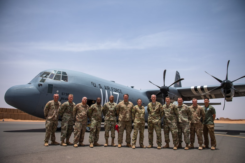 U.S. Air Force leadership from the 435th Air Expeditionary Wing and the 409th Air Expeditionary Group pose for a photo in front of a C-130J Super Hercules at Nigerien Air Base 201, Agadez, Niger, Aug. 3, 2019. This was the first C-130 to land at Air Base 201, marking the beginning of limited Visual Flight Rules operations at the base. (U.S. Air Force photo by Staff Sgt. Devin Boyer)