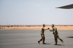 U.S. Air Force Staff Sgt. Dustin Cote, 724th Expeditionary Air Base Squadron air terminal operations center technician, left, bumps fists with Staff Sgt. John Bouscher, 86th Aircraft Maintenance Squadron flying crew chief, after the first C-130 landing at Nigerien Air Base 201, Agadez, Niger, Aug. 3, 2019. The landing marked the next step in airfield evaluations by starting Visual Flight Rules operations at the base. (U.S. Air Force photo by Staff Sgt. Devin Boyer)