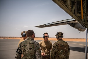 U.S. Air Force Airmen assigned to the 724th Expeditionary Air Base Squadron converse after the first military aircraft landing at Nigerien Air Base 201, Agadez, Niger, Aug. 3, 2019. The landing marked the next step in airfield evaluations by starting Visual Flight Rules operations at the base. (U.S. Air Force photo by Staff Sgt. Devin Boyer)