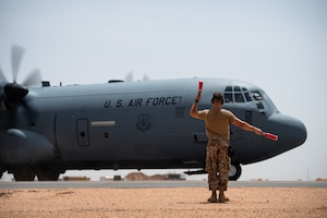 U.S. Air Force Tech. Sgt. Daniel Peterson, 724th Expeditionary Air Base Squadron air terminal operations center non-commissioned officer in charge, marshals a C-130J Super Hercules at Nigerien Air Base 201, Agadez, Niger, Aug. 3, 2019. This was the first C-130 to take-off at Air Base 201, marking the beginning of limited Visual Flight Rules operations at the base. (U.S. Air Force photo by Staff Sgt. Devin Boyer)
