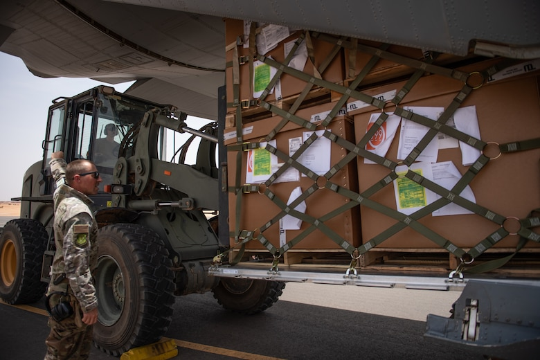 U.S. Air Force Senior Airman Steven Roy, 724th Expeditionary Air Base Squadron air terminal operations center information controller, directs Staff Sgt. Dustin Cote, 724th EABS ATOC technician, while loading a C-130J Super Hercules at Nigerien Air Base 201, Agadez, Niger, Aug. 3, 2019. This was the first C-130 to take-off at Air Base 201, marking the beginning of limited Visual Flight Rules operations at the base. (U.S. Air Force photo by Staff Sgt. Lexie West)