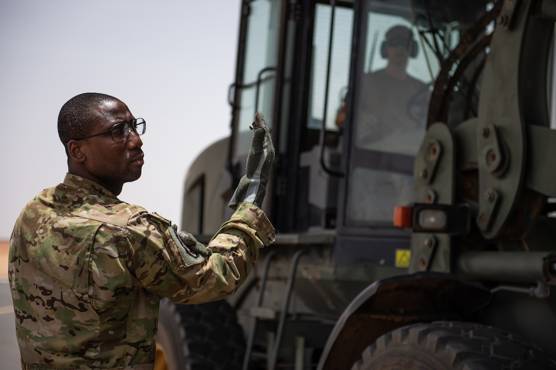 U.S. Air Force Tech. Sgt. Kellan Hyacinthe, 37th Airlift Squadron loadmaster, directs a forklift operator while loading a C-130J Super Hercules at Nigerien Air Base 201, Agadez, Niger, Aug. 3, 2019. This was the first C-130 to take-off from AB 201, marking the beginning of limited Visual Flight Rules operations at the base. (U.S. Air Force photo by Staff Sgt. Lexie West)