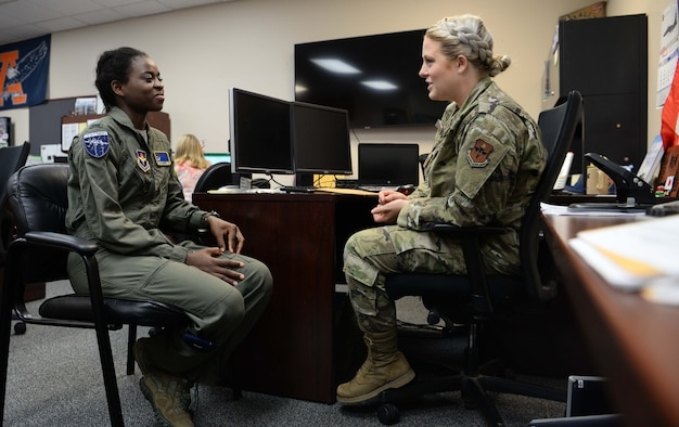 Capt. Christy Martin (right), 14th Student Squadron international military student officer, and 1st Lt. Sanni Kafayat (left), a student pilot from Nigeria, discuss Kafayat's return home July 26, 2019, at Columbus Air Force Base, Mississippi. The IMSO is tasked with managing the administrative part of an international student's training. (U.S. Air Force photo by Airman 1st Class Jake Jacobsen