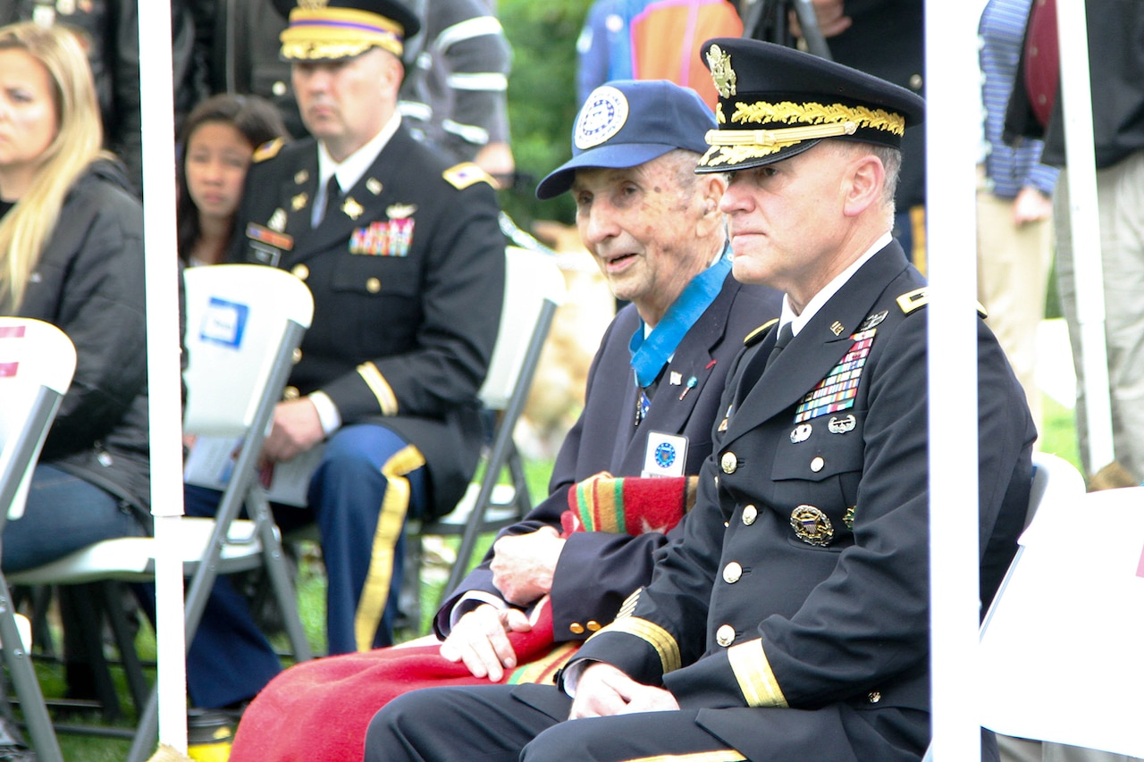 An Army lieutenant general in dress uniform sits in a folding chair next to an older veteran wearing a Medal of Honor around his neck. The older man is holding a blanket over his legs. Other people can be seen sitting in similar chairs in the background.