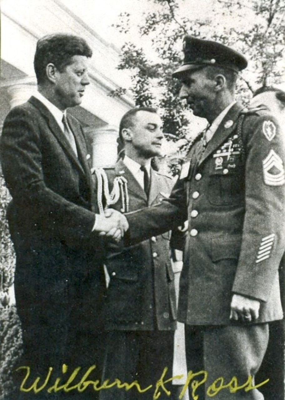 President John F. Kennedy shakes hands with an Army soldier in full dress uniform. Another soldier stands behind them looking in another direction.
