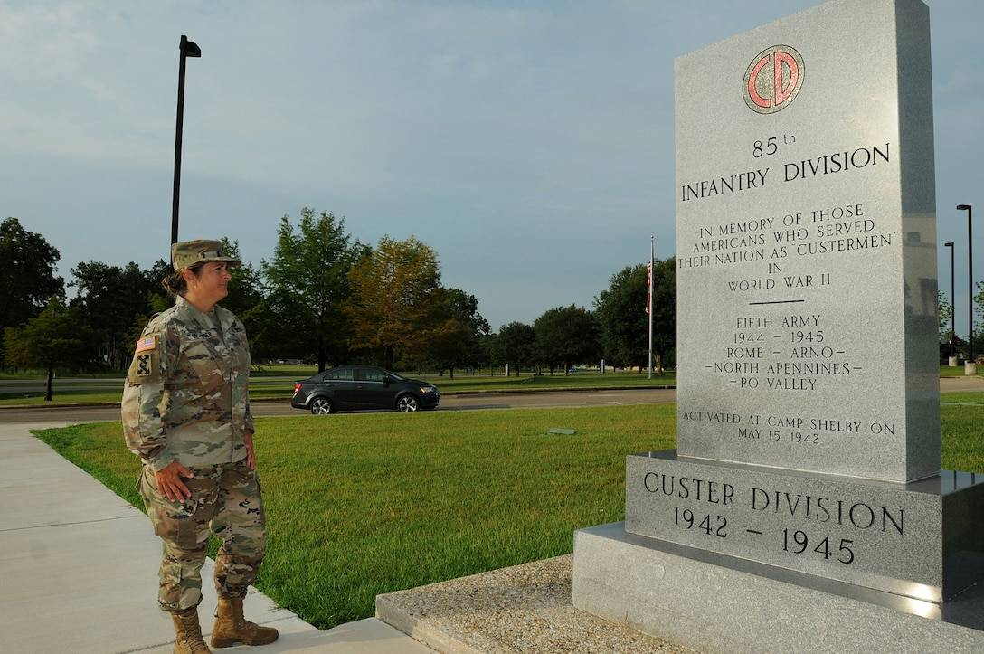 Brig. Gen. Kris A. Belanger, Commanding General, 85th U.S. Army Support Command, reflects on the command's lineage while looking at a monument at Camp Shelby, Mississippi, honoring the World War II Soldiers of the, then, 85th Infantry Division which fought overseas during World War II.