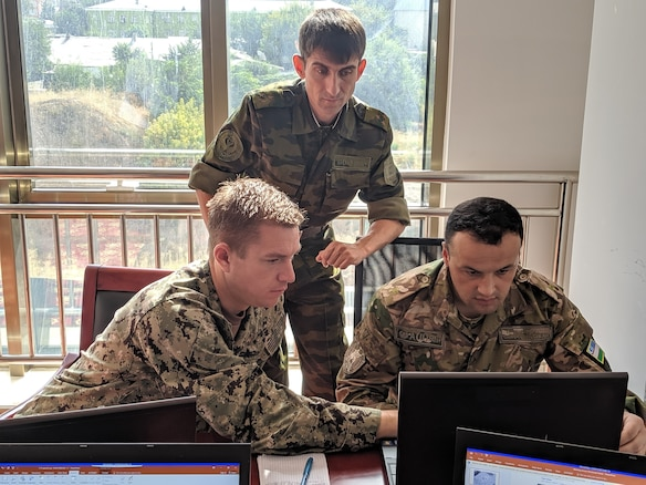 U.S. Navy Lt. Cmdr. Andrew Learned, left, special operations planner for Exercise Regional Cooperation 2019 (RC), attached to Special Operations Command Central; Tajikistan Army Col. Mehriddin Tolibzoda, center, communications officer for RC19; and Uzbekistan Army Maj. Abror Kurbanov, right, special operations engineer for RC19, collaborate on a mission plan for a fictional scenario during RC19 in Dushanbe, Tajikistan, August 13, 2019. Exercise Regional Cooperation is an annual, multinational event that promotes cooperation and interoperability among participating nations to foster security and stability in the Central and South Asian region. The participants of RC 19 include military leaders and officials from Mongolia, Tajikistan, United States and Uzbekistan and observers from Pakistan.