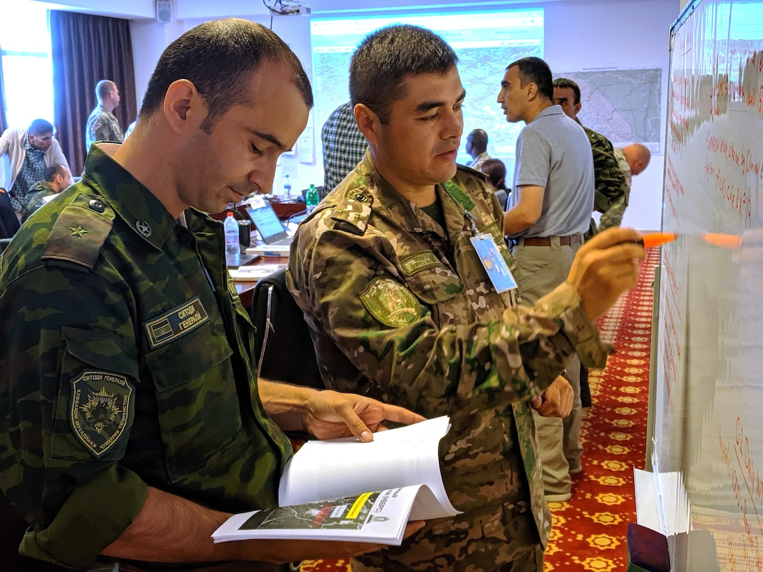 Tajikistan Army Major Said Khomushov, left, intelligence analyst for Exercise Regional Cooperation 2019, and Uzbekistan Army Lt. Col. Valijon Sattorov, right, intelligence lead for Exercise Regional Cooperation 2019, create an intelligence plan during a scenario in Exercise Regional Cooperation 2019 at Dushanbe, Tajikistan, August 14, 2019. Exercise Regional Cooperation is an annual, multinational event that promotes cooperation and interoperability among participating nations to foster security and stability in the Central and South Asian region. The exercise enhances regional security and stability among the participating nations. 