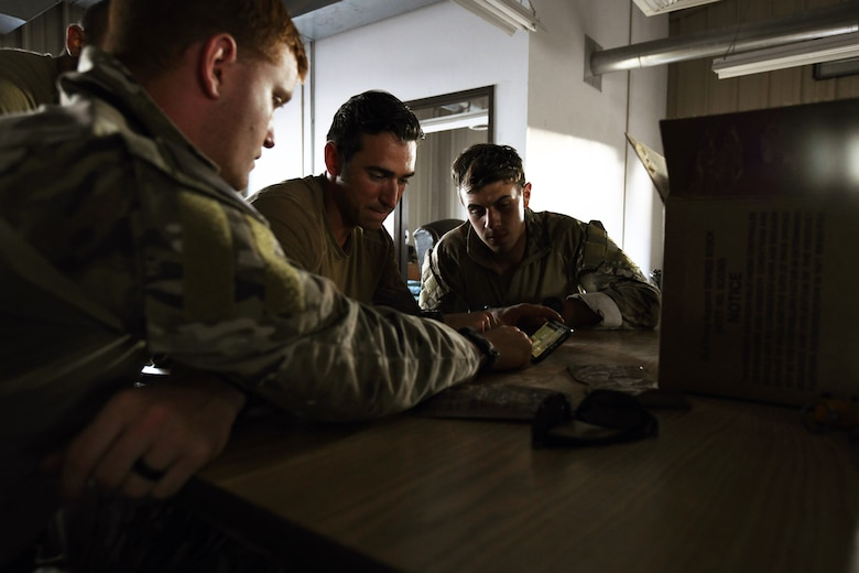 Senior Airman Jake Cook, left, 2nd Lt. Tyler Johnson and Senior Airman James Adams, Airmen from the 13th Air Support Operations Squadron, plan their route of attack in the squadron's mission qualification training July 17, 2019 on Fort Carson, Colorado. In the exercise, many of the instructors role played as the opposing force against the students. (U.S. Air Force photo by Airman 1st Class Andrew Bertain)
