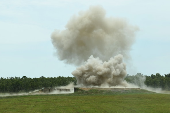 A cloud of smoke and dirt flies off a green grassy field.