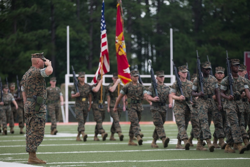 A Marine in battle dress salutes other Marines marching in formation. Those Marines are holding rifles and have a color guard following them.