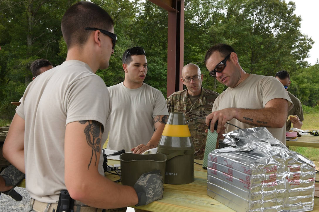 4 men look at a table that has a small green explosive object with a yellow strip.