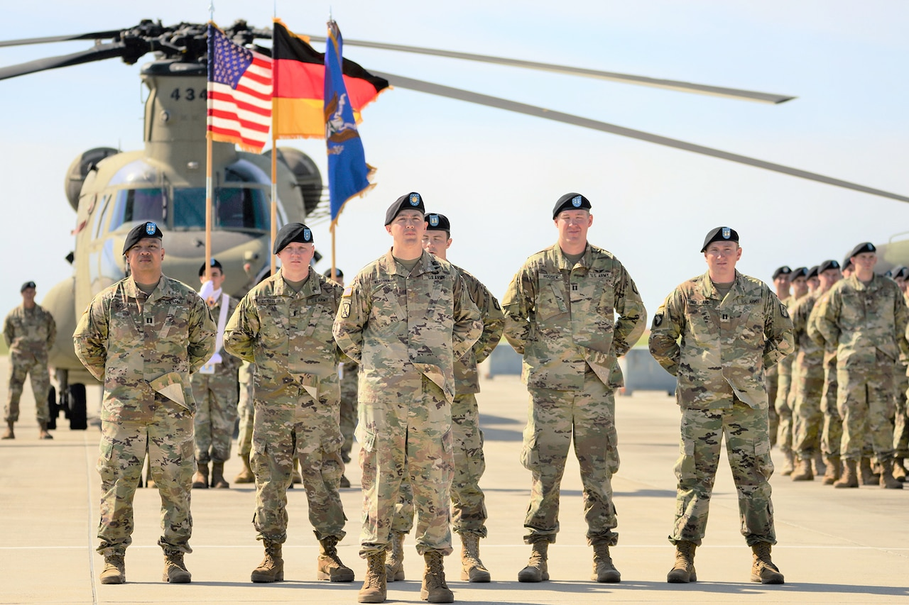 Six combat-dressed Army soldiers stand in formation with their hands behind their backs. A color guard is behind them, as is an Army helicopter. More soldiers stand in formation in the background.