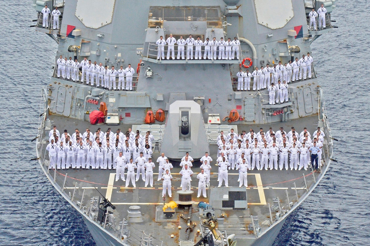 A far-away view of the front of a military destroyer ship that's filled with Navy sailors in white uniforms standing in formation with their hands behind their backs.