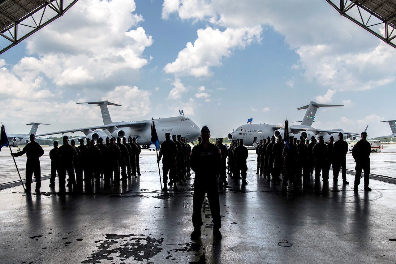 Several uniformed men whose silhouettes are shaded stand in three formations underneath an aircraft hangar. One man stands in front of them. Two large military cargo aircraft are parked behind them.