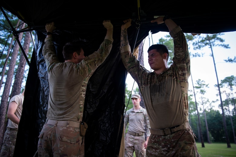 Senior Airman Tristan Wiese, left, 824th Base Defense Squadron (BDS) fire team member, and Senior Airman Fernie Salazar, 824th BDS fire team leader set up a tent during a tactical leaders course, Aug. 10, 2019, at Moody Air Force Base, Ga. The 7-day course revolved around squad leaders developing their skills to effectively communicate, team build and mission plan. These skills were assessed during a 36-hour simulated operation where squad leaders lead Airmen through tactical situations.  (U.S. Air Force photo by Airman Azaria E. Foster)