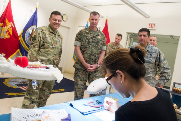 Air Force Col. Gabriel Lopez, DLA Aviation Ogden commander, left, Marine Corps Col. Larry Herring, center, and Air Force Col. John Gustafson, right, the DLA Aviation Richmond Marine Corps and Air Force Customer Facing Division chiefs, respectively, watch Helen Nguyen, DLA Troop Support Flag Room seamstress, as she hand embroiders a presidential flag Aug. 14, 2019 in Philadelphia.