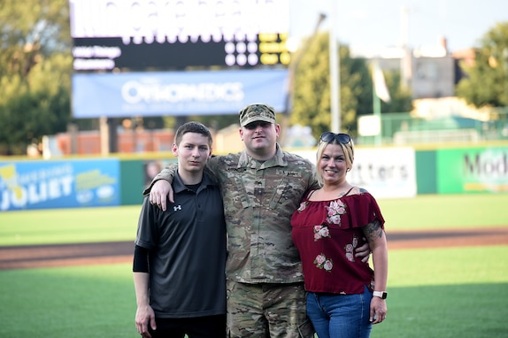 Army Reserve Staff Sgt. Clifford Arrington, Information Systems noncommissioned officer assigned to the 85th U.S. Army Reserve Support Command, pauses for a photo with his family before a Joliet Slammers home game, August 13, 2019 in Joliet, Illinois.