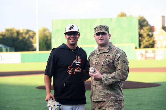 Army Reserve Staff Sgt. Clifford Arrington, Information Systems noncommissioned officer assigned to the 85th U.S. Army Reserve Support Command, pauses for a photo with Drew Peden, Pitcher for Joliet Slammers, before a Joliet Slammers home game, August 13, 2019 in Joliet, Illinois.