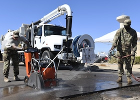 Staff Sgt. Robert Newton (left) and Tech. Sgt. Ronnie Jamison (right), 56th Civil Engineering Squadron pavements and heavy equipment operators, use an asphalt road cutter to remove chunks of asphalt Aug. 12, 2019, at Luke Air Force Base, Ariz.