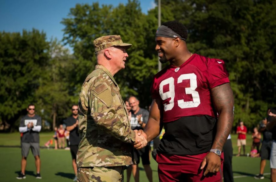 Air Force District of Washington Commander Maj. Gen. Ricky N. Rupp shakes hands with Washington Redskins defensive end Jonathan Allen Aug. 14. The team held a special walkthrough practice at Joint Base Andrews as part of ongoing Redskins Salute efforts presented by USAA.(Courtesy photo/Washington Redskins)